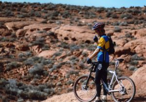 a mountain biker looking out over the red desert of southern Utah
